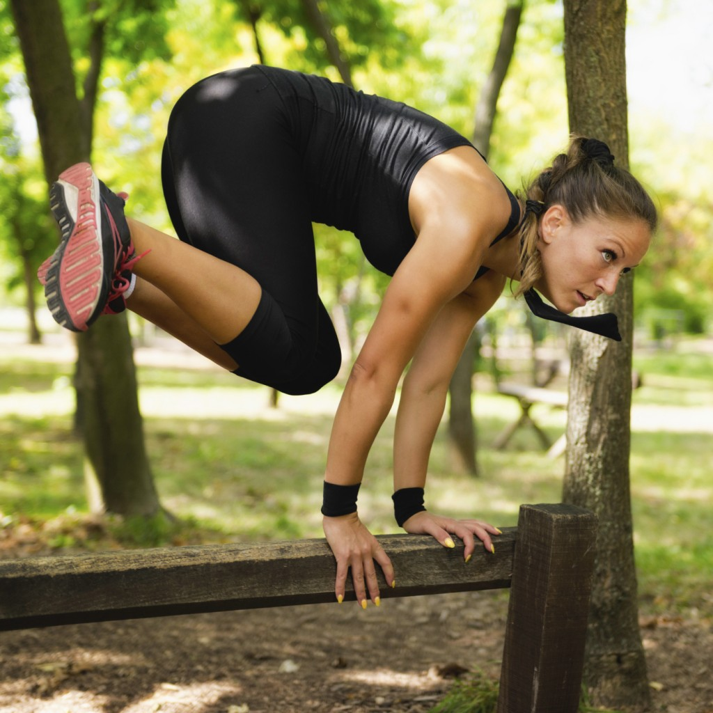 Female jumping across wooden barriers